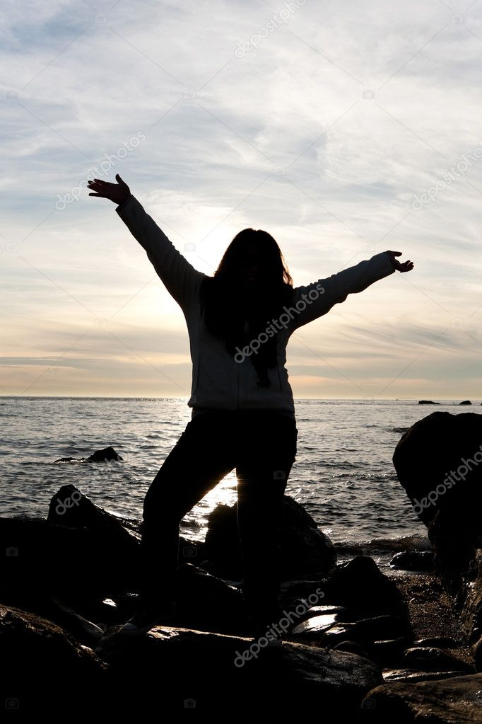 Silhouette of a young woman posing on the beach with her arms up in the air. — Stock Photo #10427569