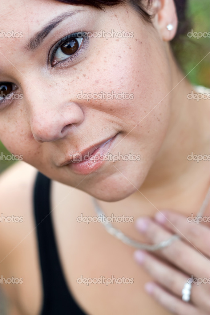 A young woman wearing a necklace and a diamond ring.  Shallow depth of field with sharp focus on her face.  Zdjcie stockowe #8695632