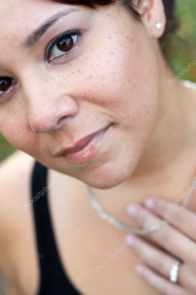 A young woman wearing a necklace and a diamond ring.  Shallow depth of field with sharp focus on her face. — Photo #8695632