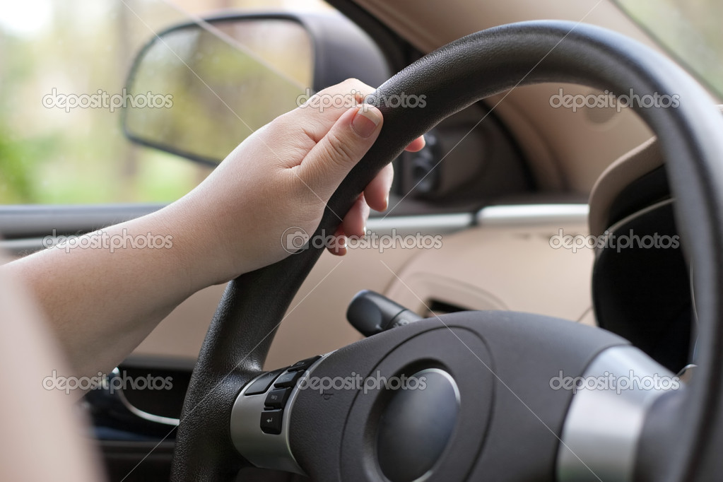 A woman holding the steering wheel of a car with one hand while driving.  Stock Photo #8696475