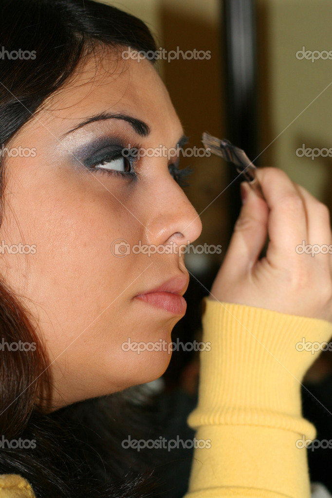 A portrait of a young hispanic woman applying eye makeup. — Stock Photo #8784596