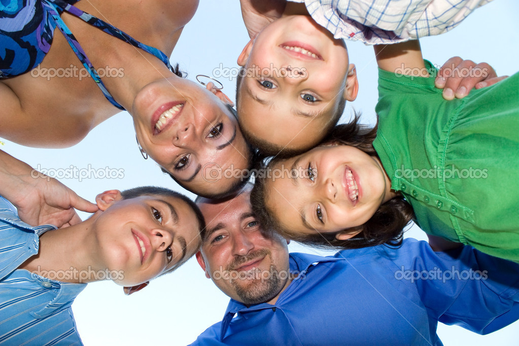 A happy family posing in a group huddle formation.  Shallow depth of field. — Stock Photo #8788635