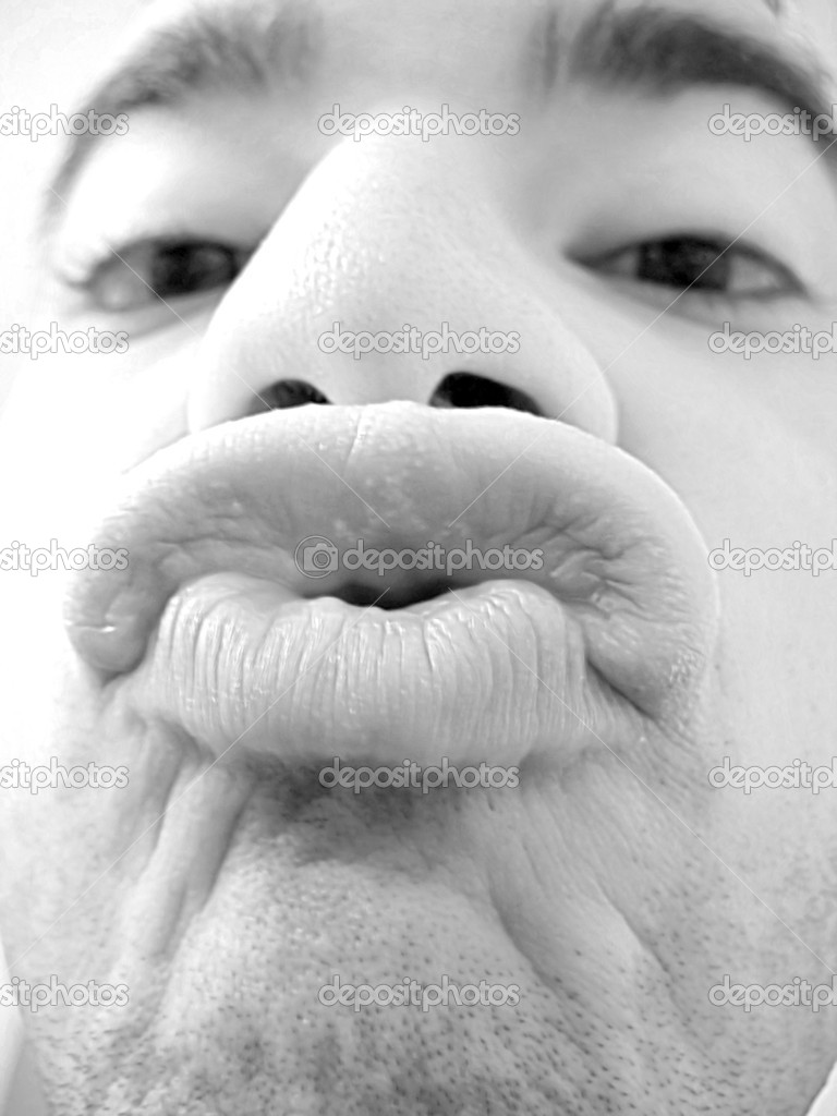 An extreme closeup of a young man trying to kiss in black and white.  Shallow depth of field. — Stock Photo #8790504
