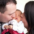 Foto Stock: Happy Parents Kiss Their Newborn Baby