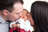 Felices padres besan a su bebé recién nacido — Foto de Stock