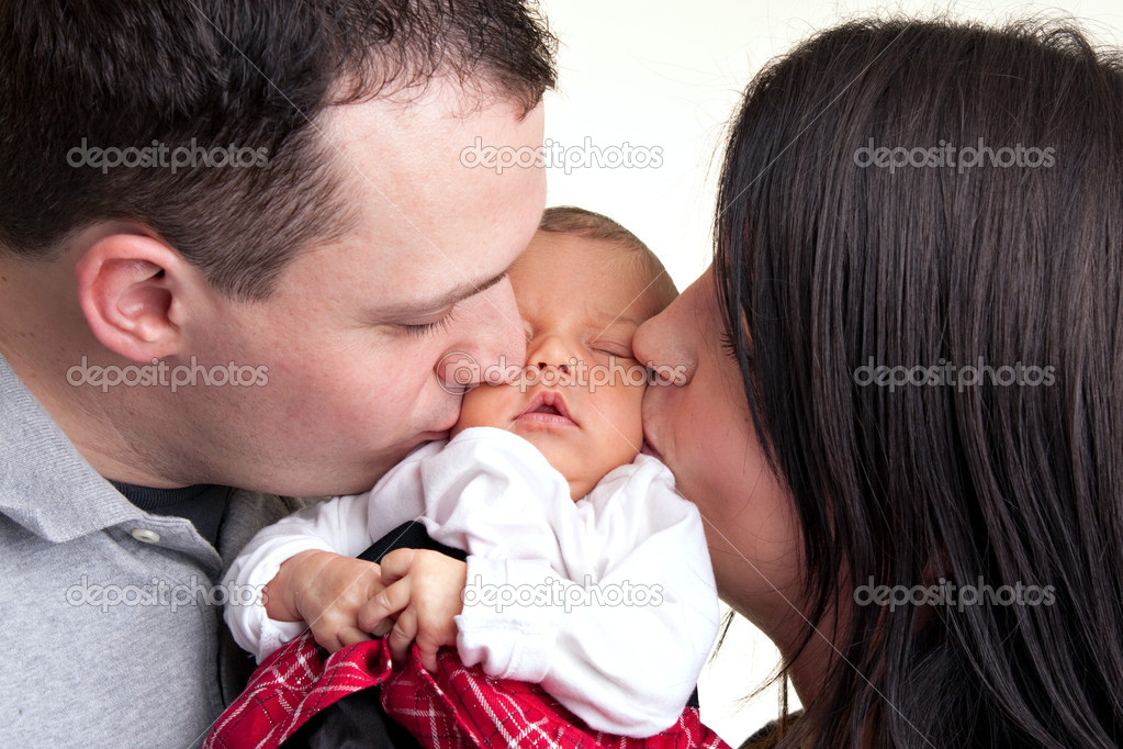 A newborn baby is held by her mother and father as they kiss her cheeks. — Stock Photo #8943935
