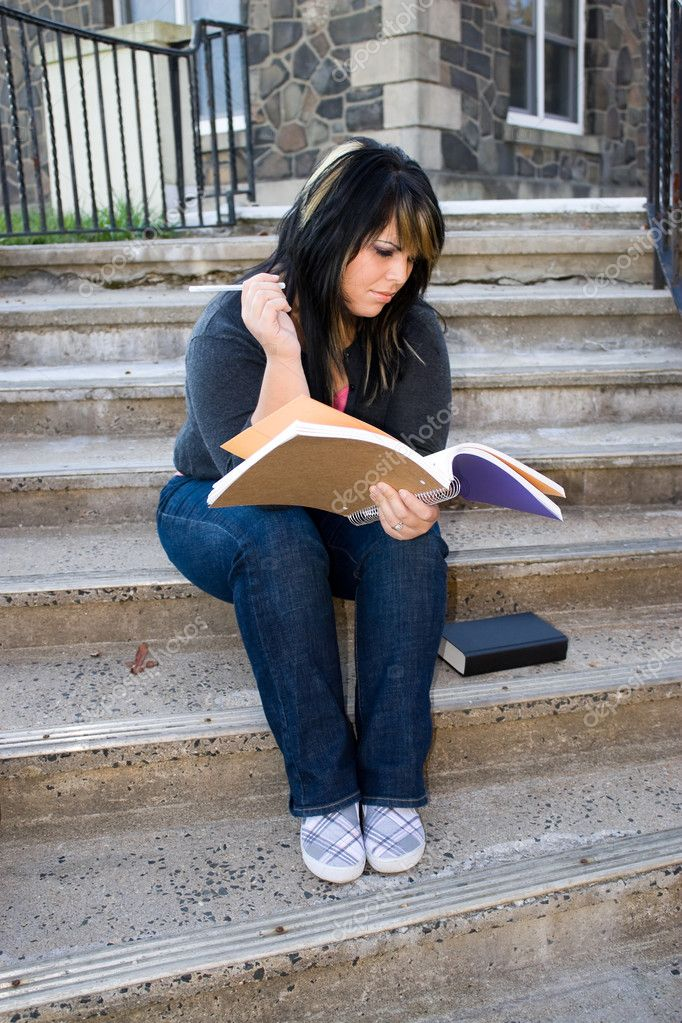 A young woman looking at her notebook while sitting on the campus stairs. — Stock Photo #8944263