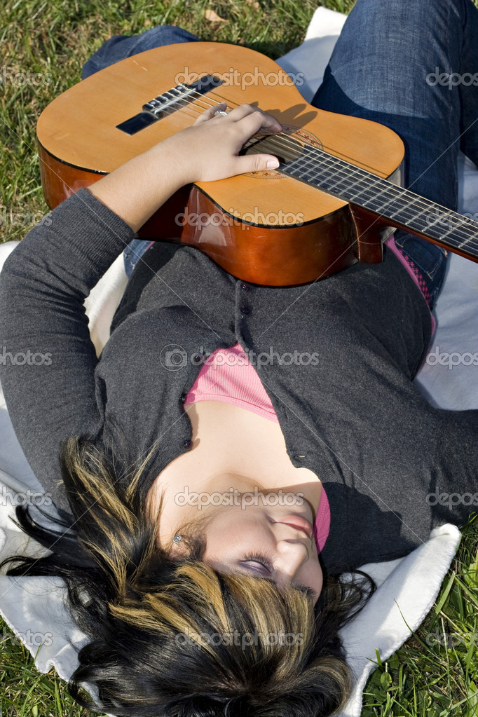 A young hispanic woman playing a guitar while laying on a blanket in the green grass.  Her hair is highlighted with blonde streaks.  Stock Photo #8944408