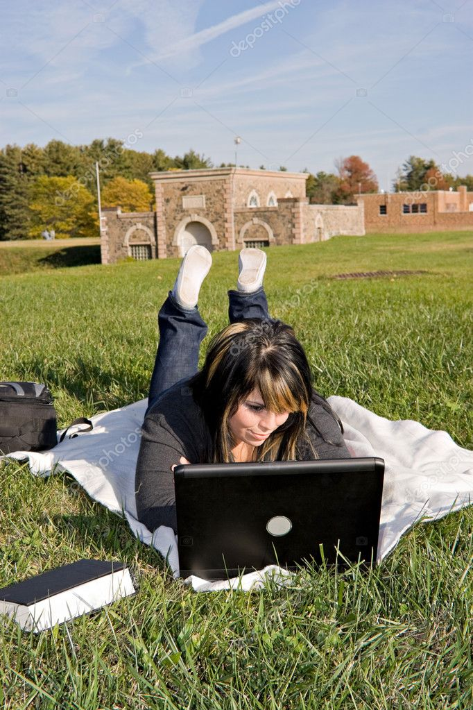 A young student using her laptop computer while laying in the grass on a nice day.  Stock Photo #8944453