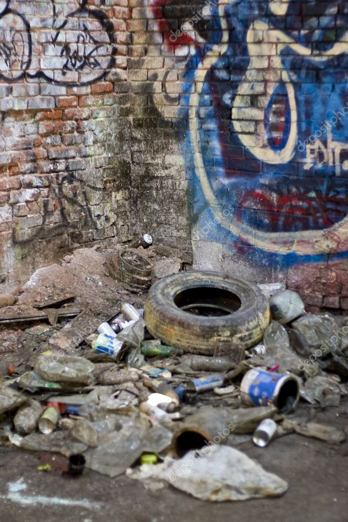 An abandoned area that is covered with trash and street graffiti.  This makes an excellent background or backdrop.  Shallow depth of field. — Stock Photo #8946520