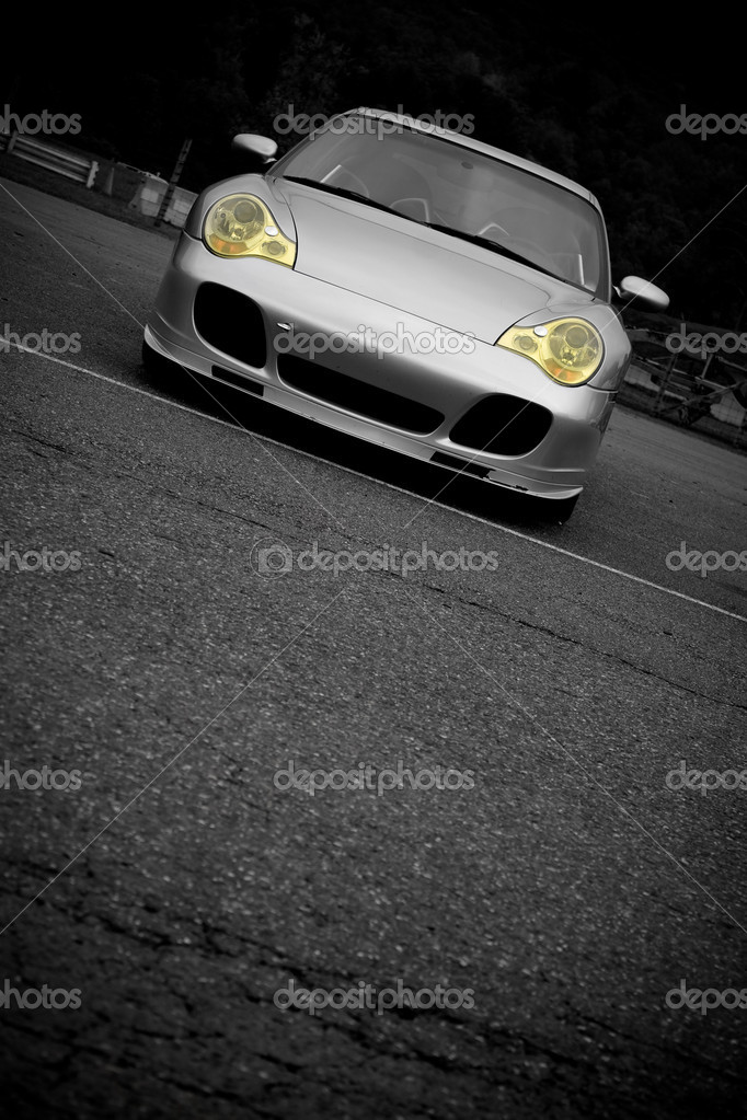 A silver sports car with the yellow headlights highlighted in selective color.  Plenty of copyspace for your text. — Stock Photo #9240118