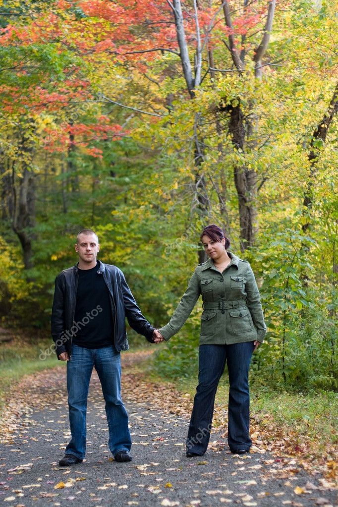A young happy couple on a path in the woods during Autumn. — Stock Photo #9240390