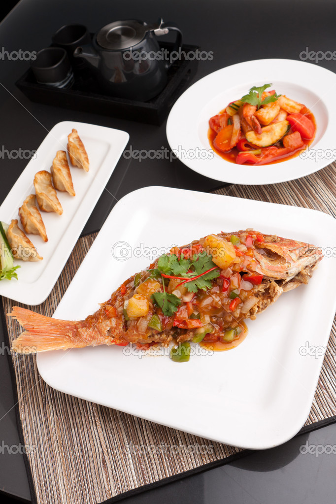 Freshly prepared Thai style whole fish red snapper dinner with sweet and sour shrimp and pan fried gyoza dumplings appetizer.  Stock Photo #9801363