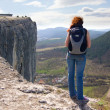 A girl standing on the edge of the high mountain and looking ahe — Stock Photo