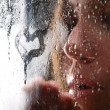 A girl slooking through the wet glass — Stock Photo