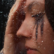 A girl is thinking standind behind the glass on one of rainy day — Stock Photo