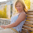 Stock Photo: Young woman's sitting on bench under rays of fading su
