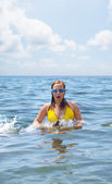 A young girl wearing yellow swimsuit swims in the sea — Stock Photo
