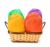Four yarn skeins in yellow, orange, green, purple colors in bask — Stock Photo