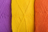 Background of yarn skeins in yellow, orange and purple colors — Stock Photo