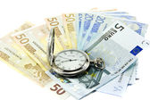 Euro banknotes and antique clock — Stock Photo