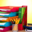 Bright paper trays and stationery on wooden table on yellow background — Stock Photo #10014833