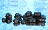 Spa stones with droplets on blue background — Stock Photo