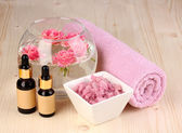 Vase with roses, spa setting on wooden background — Stock Photo