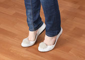 Legs in jeans and ballet flat shoes on wooden background — Stock Photo