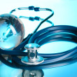Globe and stethoscope on blue - Foto de Stock