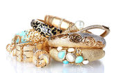 Beautiful golden bracelets and rings isolated on white — Stock Photo