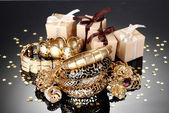 Güzel altın takı ve gri arka plan üzerinde hediyeler — Stok fotoğraf