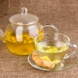 Healthy ginger tea in kettle and cup on sackcloth - Stock Photo