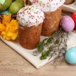 Beautiful Easter cakes, colorful eggs in basket and candles on wooden table - Foto Stock