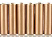 Golden batteries isolated on white — Stock Photo