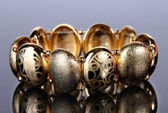 Mooie gouden armband op grijze achtergrond — Stockfoto
