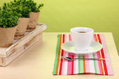 Coffee cup on table in cafe on green background — Stock Photo