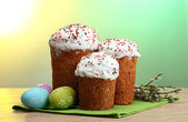 Beautiful Easter cakes, colorful eggs and pussy-willow twigs on wooden table on green background — Stock Photo