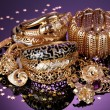 Beautiful golden jewelry on purple background — Stock Photo