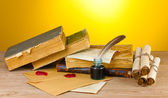 Staré knihy, svitky, peří pero a inkwell na dřevěný stůl na žlutém podkladu — Stock fotografie