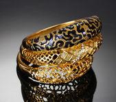 Lindas pulseiras douradas sobre fundo cinzento — Foto Stock