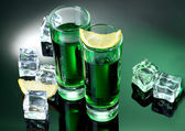 Two glasses of absinthe, lemon and ice on green background — Stock Photo