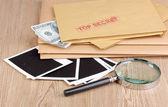 Envelopes com selo secreto superior com papéis fotográficos e lupa em fundo de madeira — Fotografia Stock