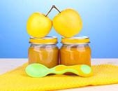 青色の背景にナプキンにスプーンで赤ちゃんの jar ファイルのピューレします。 — ストック写真