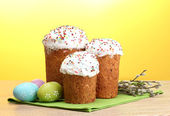 Beautiful Easter cakes, colorful eggs and pussy-willow twigs on wooden table on yellow background — Stock Photo
