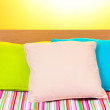 Bright pillows on bed on yellow background — Stock Photo