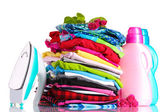 Pile of colorful clothes and electric iron with detergent isolated on white — Stock Photo