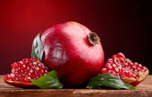 Ripe pomegranate fruit with leaves on wooden table on red background — Stock Photo