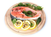 Red fish with lemon and parsley on wooden cutting board isolated on white — Stock Photo