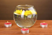 Spa composition of bright candles and yellow chrysanthemum floating on wooden background — Stock Photo
